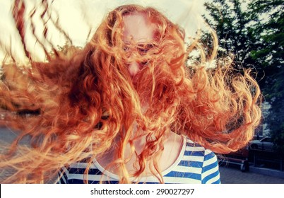 Portrait of a beautiful redhead girl with flying hair in the wind outdoors. Young casual girl with wavy hair. Redhair woman with messy windy tousy blowsy hair, long wavy hair fly in the wind