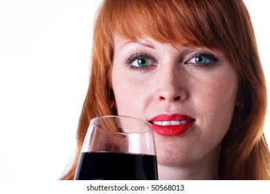 Portrait of a beautiful redhead girl with a glass of red wine