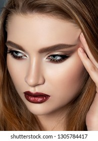 Portrait of beautiful redhead woman with evening makeup touching her face. Golden smokey eyes and dark read lips. Luxury skincare and modern fashion makeup concept. Studio shot.
