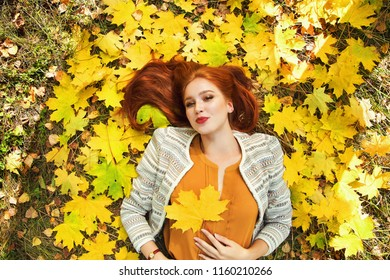 portrait of a beautiful redhead woman with yellow maple leaves in autumn