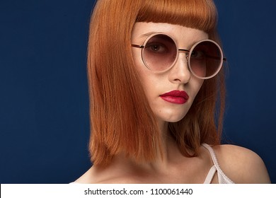 ad0d9e8b2c2f Portrait of beautiful redhead young woman wearing fashionable sunglasses.  Girl in glamour makeup. Haircut