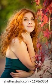 Portrait of beautiful redheaded woman walking outdoors in autumn