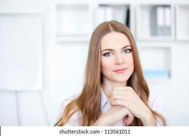 Portrait of beautiful relaxed young business woman smiling at office