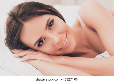 Portrait of beautiful relaxed young woman dreaming in bed