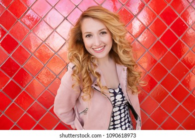 Portrait of beautiful retro young woman looking smiling against bright vivid red tiles background, quirky dynamic americana style, outdoors. Vintage female fun playful lifestyle, leisure.