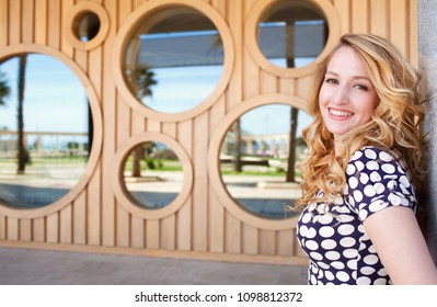 Portrait of beautiful retro young woman posing, looking smiling at camera with wooden stripes and glass circles with reflections, graphic outdoors. Fun playful vintage leisure recreation lifestyle.