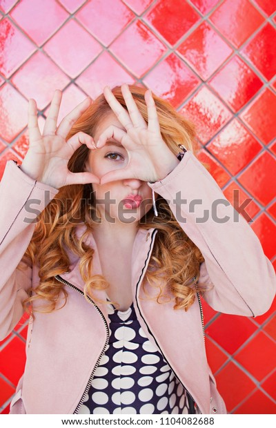 Portrait of beautiful retro young woman looking smiling making heart shape with hands, kissing against bright red tiles background, americana style, outdoors. Love symbol, fun playful lifestyle.