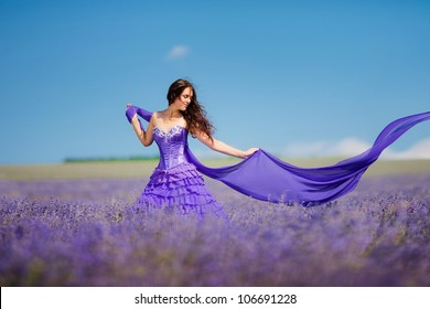 Portrait of beautiful romantic woman in fairy field of lavender with a colored tissue