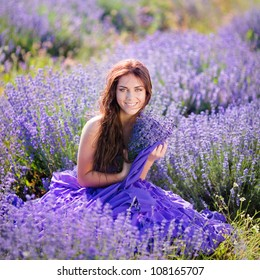 Portrait of beautiful romantic woman in fairy field of lavender with bouquet