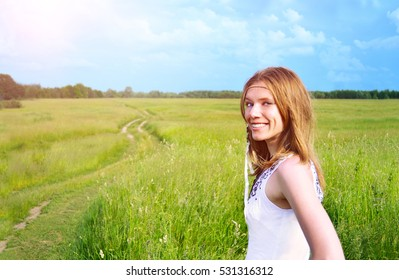 Portrait of beautiful romantic woman outdoor. Road and forest on the background.