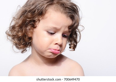 Portrait of a beautiful sad boy. Toddler feeling sadness because he was disappointed. Adorable boy having different emotions. Kid making funny faces. Boy with long curly hair.