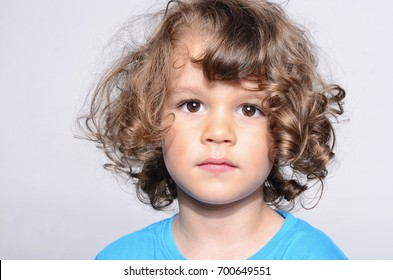Portrait of a beautiful sad boy. Toddler felling sadness because he was disappointed. Adorable boy having different emotions. Boy with long curly hair.