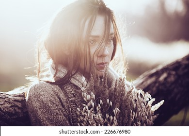 Portrait of a beautiful sad brunette girl outdoors in autumn