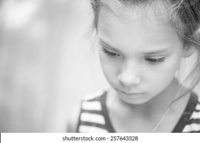 Portrait of beautiful sad little girl close-up. Black and white photo.