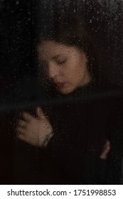 Portrait of beautiful sad woman in rainy weather looking through glass with raindrops, autumn melancholy concept.