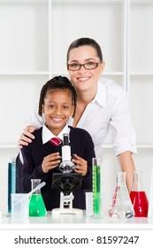 portrait of beautiful science teacher and schoolgirl in lab