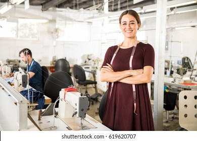 Portrait of a beautiful seamstress carrying a tape measure and working in a textile factory
