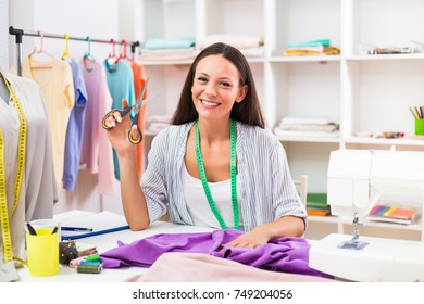 Portrait of beautiful seamstress showing scissors and working  at her workshop.Dressmaker working