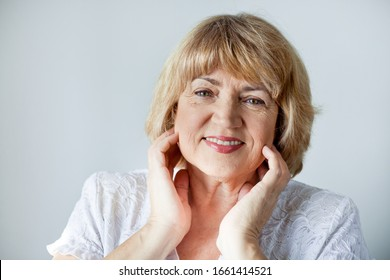 Portrait of a beautiful senior blonde woman of European race on a white background, close-up