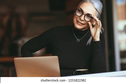 Portrait of beautiful senior businesswoman sitting at cafe with laptop looking away and thinking. Mature woman at coffee shop.
