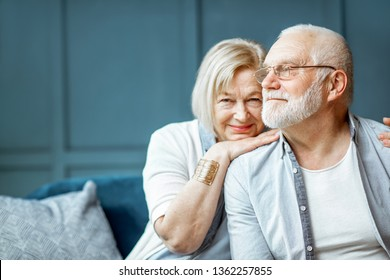 Portrait of a beautiful senior couple embracing each other, sitting on the couch at home