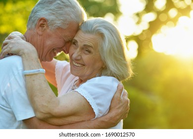 Portrait of beautiful senior couple huging in the summer park