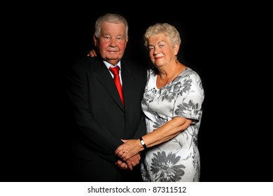 A portrait of a beautiful senior couple standing together over black background