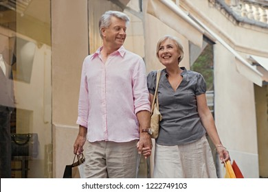 Portrait of beautiful senior couple walking in shopping street carrying bags, vacation trip outdoors. Mature consumer people in expensive city break travel, leisure recreation lifestyle.
