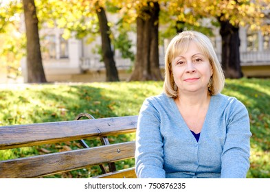 Portrait of beautiful senior happy elderly middle-aged blond woman sitting on a bench in the park looking at the camera on the autumn spring background on a sunny day.