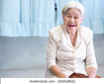 Portrait of beautiful senior or old woman with white hair smiling Blue curtain background : concept  happy
