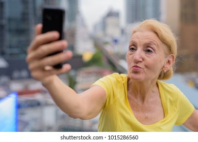 Portrait of beautiful senior woman with blond hair against view of the city