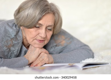 Portrait of beautiful senior woman with book