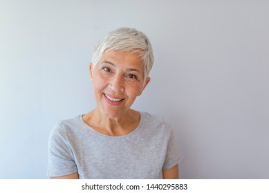 Portrait of beautiful senior woman in front of grey background. Portrait of a beautiful elderly woman, smiling, isolated on grey background. Anti-aging and beauty concept.