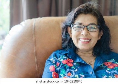 Portrait of beautiful senior woman with glasses and smile  relaxing in living room at home.