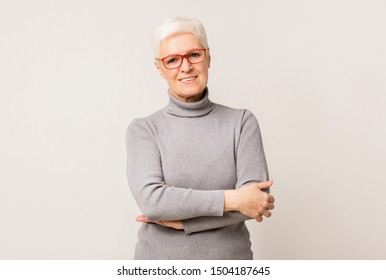 Portrait of beautiful senior woman in glasses standing with folded arms over light studio background with free space