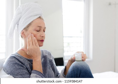 Portrait of beautiful senior woman putting on the cream.