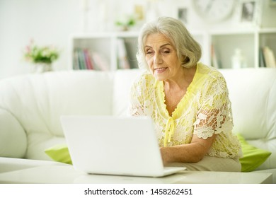 Portrait of beautiful senior woman sitting at table with laptop