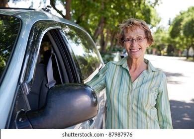 Portrait of beautiful senior woman standing near car