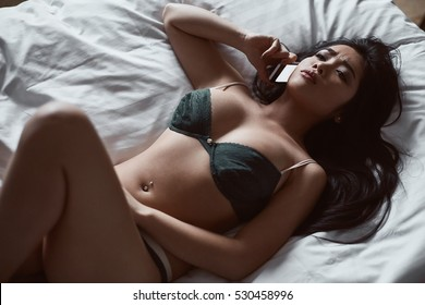Portrait of a beautiful sensual asian woman in underwear lying on the bed with the phone in his hand. Interior shot
