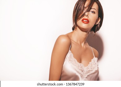Portrait of beautiful sensual brunette woman. Girl in elegant beige classic clothes. Model with red lips isolated on white