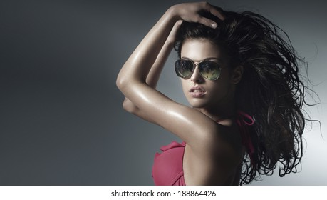 Portrait of beautiful sensual brunette woman with long curly hair and sunglasses