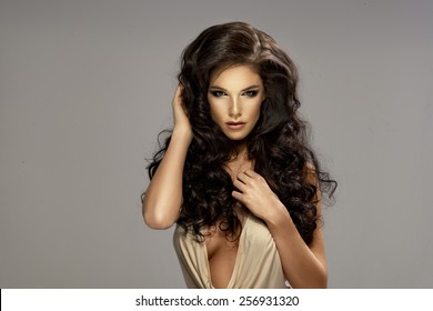 Portrait of beautiful sensual brunette woman with long curly hair. Beauty photo.