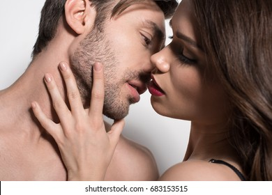 Portrait of beautiful sensual couple embracing and kissing isolated on white