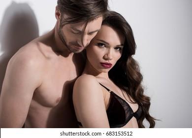 Portrait of beautiful sensual couple hugging on grey background