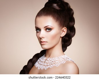 Portrait of beautiful sensual woman with elegant hairstyle.  Perfect makeup. Girl pigtailed. Fashion photo