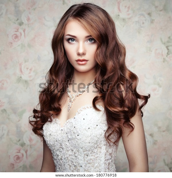 Portrait of beautiful sensual woman with elegant hairstyle. Wedding dress. Fashion photo