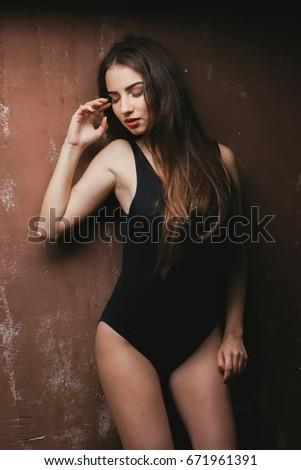 98d32f4e2 portrait of beautiful sensual woman wearing black lingerie bodysuit on wall  background. sexy woman wearing