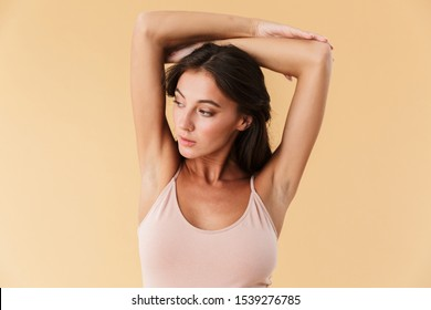 Portrait of a beautiful sensual young brunette woman wearing swimsuit isolated over beige background, posing
