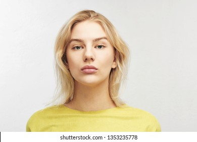 Portrait of beautiful serious European girl on white background Isolated. Attractive blonde business woman in yellow clothes looks into the camera busily