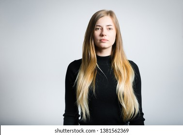 portrait of a beautiful serious girl, studio photo over gray background